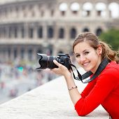 Portrait of a pretty young tourist taking photographs while sightseeing in Rome, Italy (with Colosse