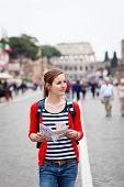 Pretty young female tourist holding a map while walking along the Via del Fori Imperiali avenue in R