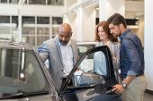 Mature african salesman showing all the car features to young couple. Car dealer showing new car to  poster