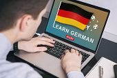 Man Working On Laptop With Learn German On A Screen. Education Learning German Language School Conce poster