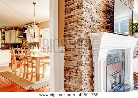 Stone Fireplace With Tv And Dining Room And Kitchen.
