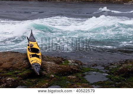 Ocean kayak beached on rocky shore at tidal rapids