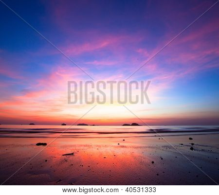 Sunset over ocean at low tide