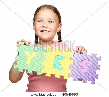 Menina bonitinha está segurando o slogan sim, isolado sobre o branco