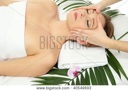 Portrait of beautiful woman in spa salon taking head massage