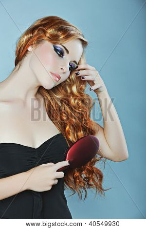 beautiful woman brushing long curly red hair over her shoulder �¢?? focus on the hair