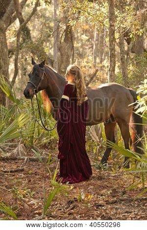 beautiful woman in medieval dress with horse in forest