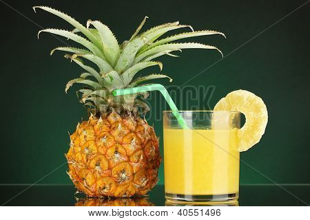 Ripe pineapple and juice glass on dark green background