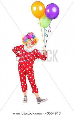 Full length portrait of a male clown in costume holding bunch of balloons isolated on white background