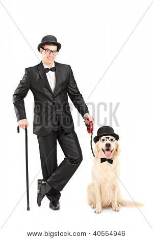 Full length portrait of a magician with bow tie holding cane and dog isolated on white background