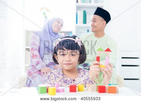 Muslim child building wooden house. Southeast Asian girl playing woodblock house at home.