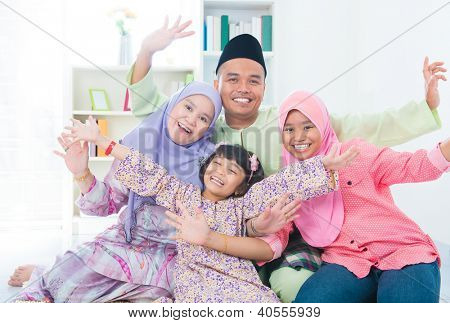 Excited Southeast Asian family at home. Muslim family living lifestyle.
