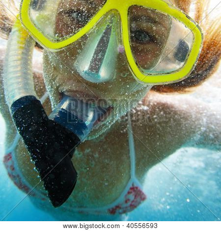 Extreme close up underwater portrait of a woman with snorkeling gear and with a lot of bubbles on face