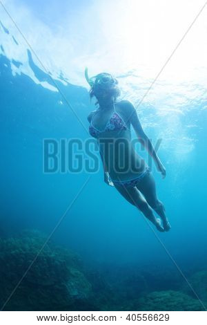 Young woman doing skin diving in a tropical sea