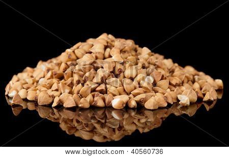 Whole buckwheat heap isolated on black background