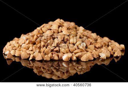 Whole buckwheat heap isolated on black background