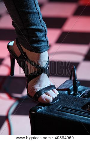 Part of leg of woman stepped on amplifier in studio with checkered background in pink light.