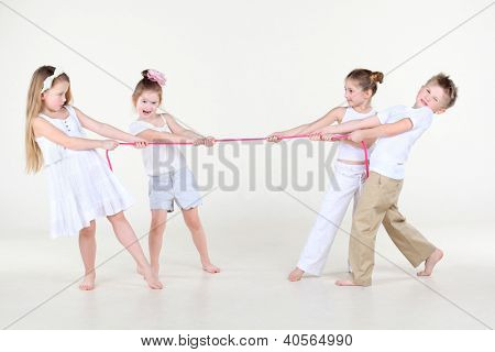 Four cute little boys and girls in white clothes overtighten pink rope.