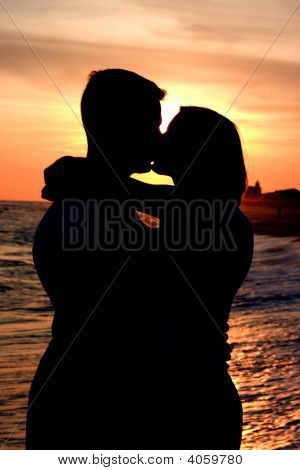 A Man And Woman Kiss At Sunset
