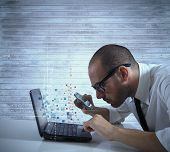 stock photo of byte  - Businessman looking for virus and hacking in a laptop - JPG