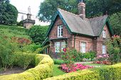 stock photo of english cottage garden  - Small cottage surrounded by a beautiful garden - JPG