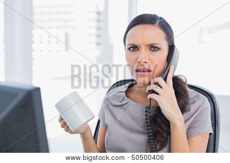 Irritated secretary answering phone in her office