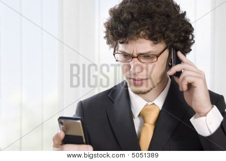Troubled Business Man With Two Mobile Phone