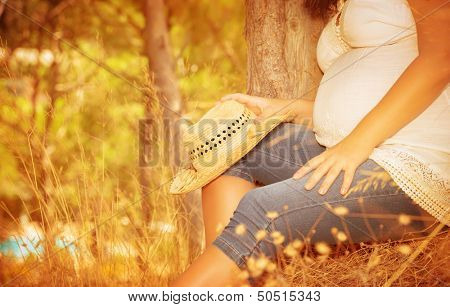 Pregnant girl sitting in autumnal park, body part, tummy of expectant woman, spending time in countryside, healthy pregnancy concept