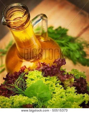 Olive oil and fresh green vegetables on wooden table, tasty salad dressing, lettuce leaves, organic nutrition, healthy eating concept