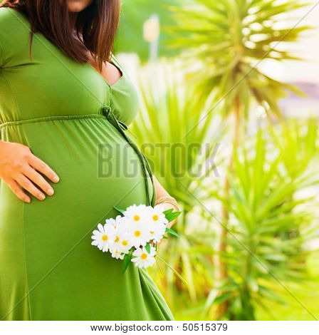 Expectant female in tropical park, body part, abdomen of pregnant woman, daisy flowers, healthy pregnancy, new life concept