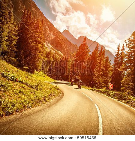 Motorcyclists on the mountainous road in bright red sunset light, riding on highway pass along Alpine mountains, enjoying extreme sport, travel and tourism