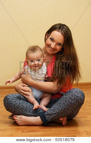 Young mother playing with her son at home.