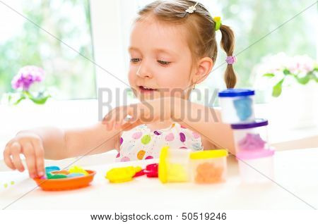 Child Is Playing With Colorful Dough