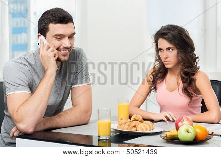 couple having breakfast, guy talking on the phone