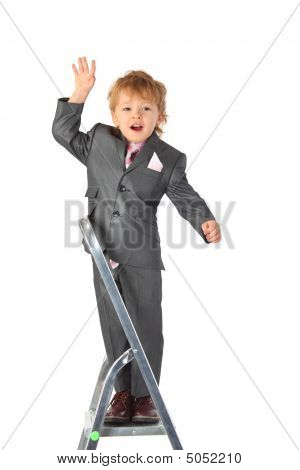 Boy In Suit Balances At Step-ladder Top