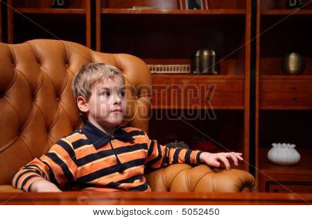 Boy Sits In Leather Armchair In Luxury Office