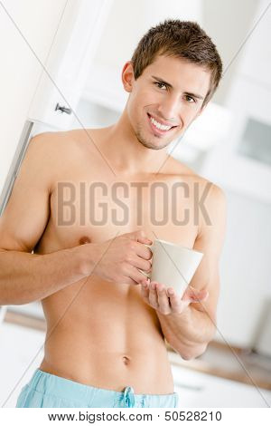 Half-naked man keeping cup of tea stands at kitchen leaning on the fridge