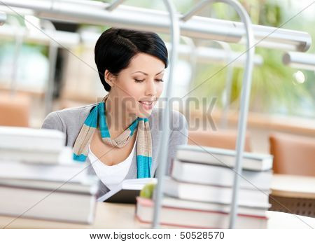 Woman surrounded with piles of books reads sitting at the table at the library. Knowledge concept
