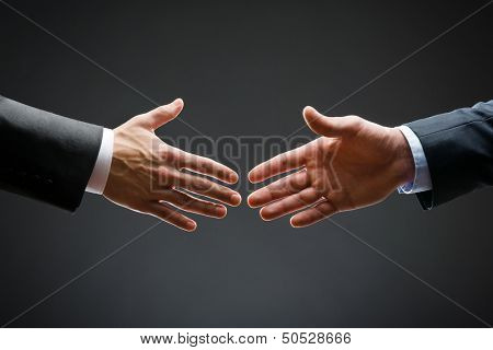 Close up of forthcoming handshake of business people. Concept of trustworthy relations and business cooperation
