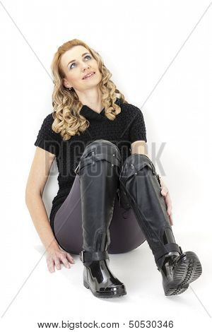 sitting woman wearing black clothes and black boots