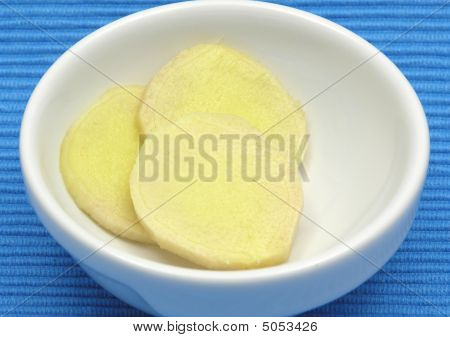 Ginger In A Bowl Of Chinaware On Blue Background
