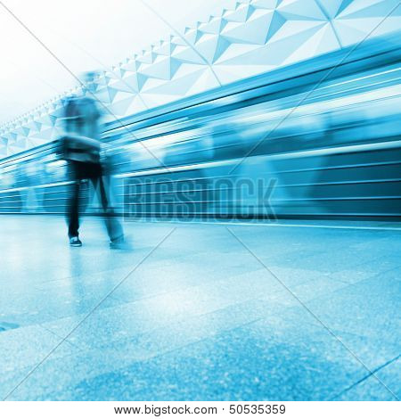 Motion blurred passenger walking in subway station.