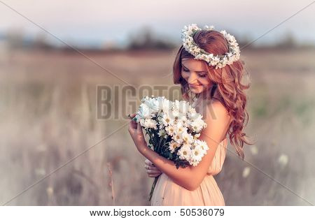 beautiful girl in a camomile wreath