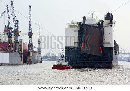 Tugboat Behind Roro-/container Ship At Hamburg Harbour