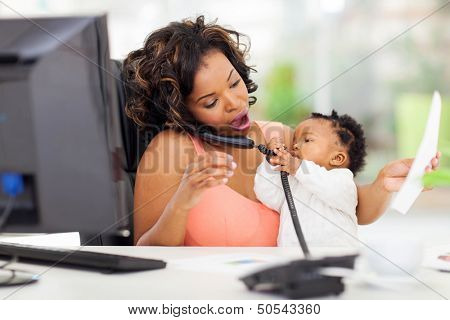 busy african businesswoman with baby girl working in office