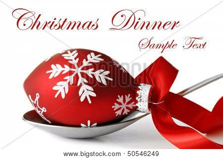 Christmas dinner concept.  Stainless steel serving spoon with Christmas ornament and satin ribbon on white background with copy space.