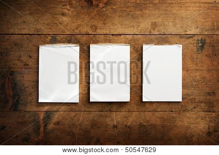Three used memo pads on an old grungy wooden surface. For inserting your messages.