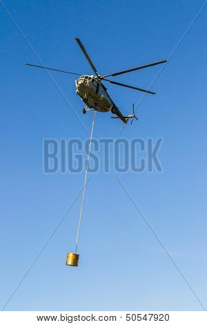 Helicopter in action carrying the water bucket. Shot from the ground.