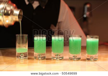 Barman Serving Green Alcohol Shots.