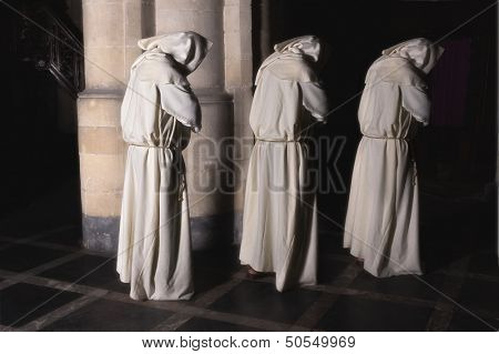 Hooded monks walking in a dark medieval church